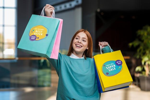 Szczęśliwa kobieta podnosi jej papierowe torby w centrum handlowym
