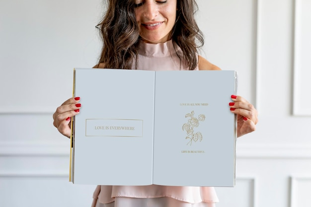 Szczęśliwa kobieta trzyma makieta książki z kwiatowym tekstem miłości