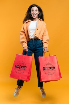 Szczęśliwa kobieta trzyma torby na zakupy