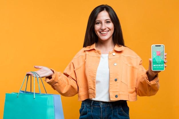 Szczęśliwa kobieta trzymając torby na zakupy i makiety telefonu