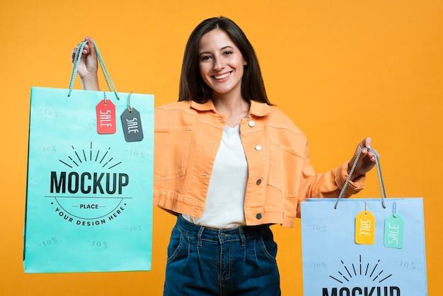 Szczęśliwa kobieta trzymając torby na zakupy z makietami tagów