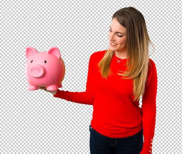 Szczęśliwa młoda blondynki kobieta trzyma piggybank