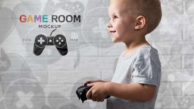 Szczęśliwa młoda chłopiec bawić się na konsoli