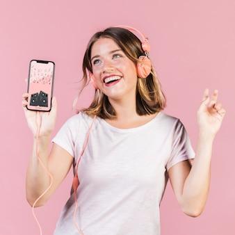 Szczęśliwa młoda kobieta z hełmofonami i telefonu komórkowego egzaminem próbnym