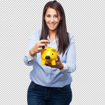 Szczęśliwa młoda kobieta z prosiątko bankiem