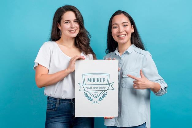 Szczęśliwe dziewczyny trzymając makietę tablicy