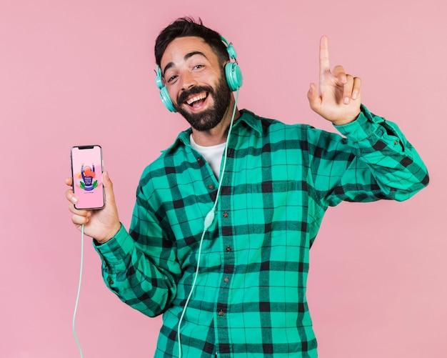 Szczęśliwy brodaty mężczyzna z hełmofonami i telefonem komórkowym wyśmiewa up