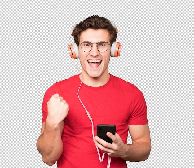 Szczęśliwy młody człowiek gestem świętowania. korzystanie ze słuchawek i trzymanie smartfona