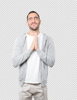 Szczęśliwy młody człowiek modląc się gest