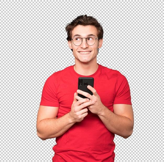 Szczęśliwy młody człowiek patrząc w górę i za pomocą telefonu komórkowego