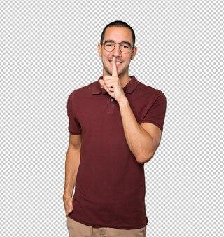 Szczęśliwy młody człowiek prosi o ciszę, gestykulując palcem