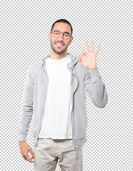 Szczęśliwy młody człowiek robi dobrze gest