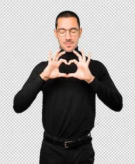 Szczęśliwy młody człowiek robi gest miłości rękami