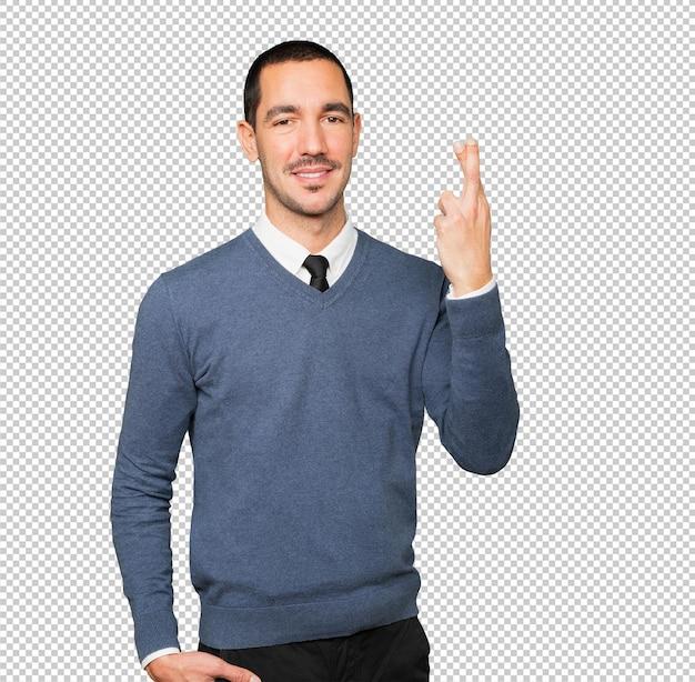 Szczęśliwy młody człowiek robi gest skrzyżowanymi palcami