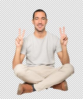 Szczęśliwy młody człowiek robi gest zwycięstwa palcami