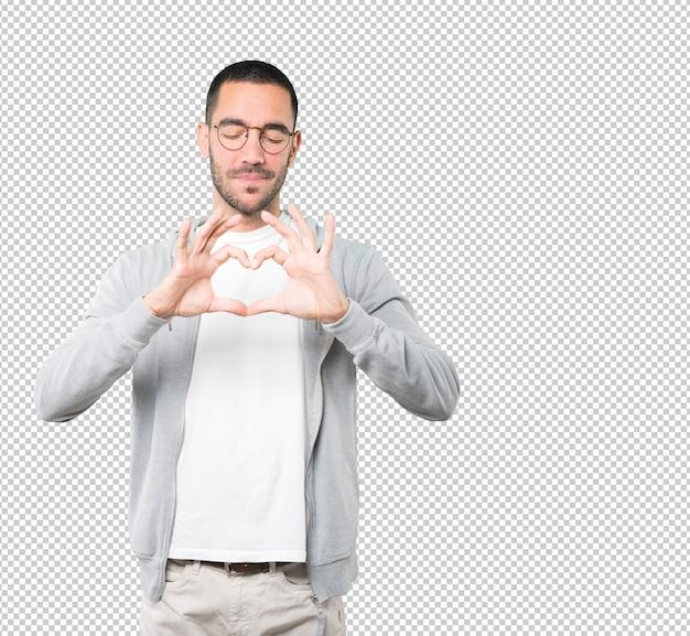 Szczęśliwy młody człowiek robi gestowi miłości z jego rękami
