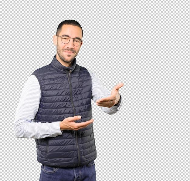 Szczęśliwy młody człowiek robi gestowi powitania z jego ręką