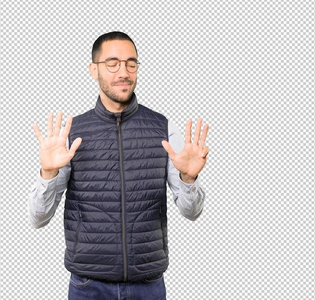 Szczęśliwy młody człowiek robi numerowi dziewięć gestowi z jego rękami