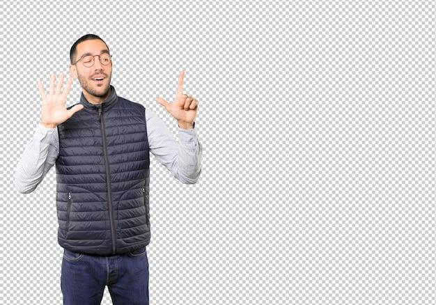 Szczęśliwy młody człowiek robi numerowi siedem gestowi z jego rękami