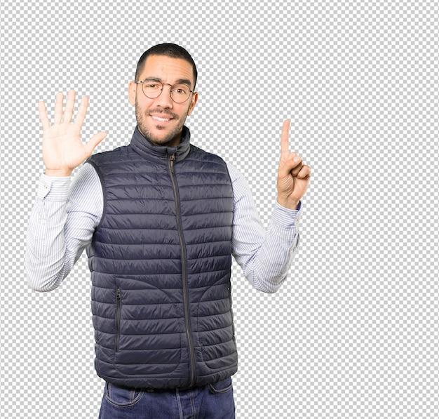 Szczęśliwy młody człowiek robi numerowi sześć gestowi z jego rękami