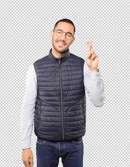 Szczęśliwy młody człowiek robi skrzyżowanym palca gestowi