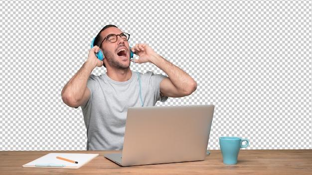 Szczęśliwy młody człowiek siedzi przy biurku i za pomocą słuchawek