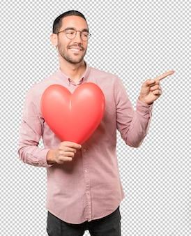 Szczęśliwy młody człowiek trzyma dużego zabawkarskiego serce i robi gestom o walentynka dniu