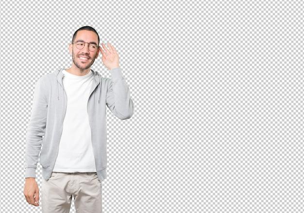 Szczęśliwy młody człowiek uśmiecha się gest i próbuje coś usłyszeć