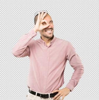Szczęśliwy młody człowiek używa jego ręki jak lornetki