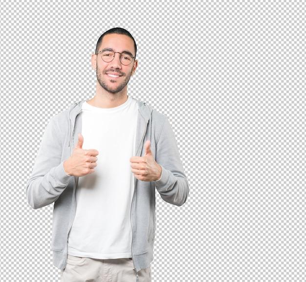 Szczęśliwy młody człowiek, wskazując, że wszystko jest w porządku