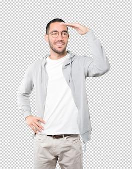 Szczęśliwy młody człowiek z gestem odwracając wzrok