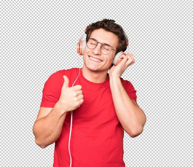 Szczęśliwy młody człowiek za pomocą słuchawek i smartfona z dobrym gestem