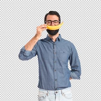 Szczęśliwy młody modnisia mężczyzna z bananem