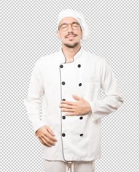 Szczęśliwy młody szef kuchni myśleć o jedzeniu