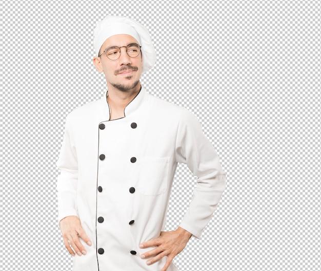 Szczęśliwy młody szef kuchni pozuje przeciw tłu