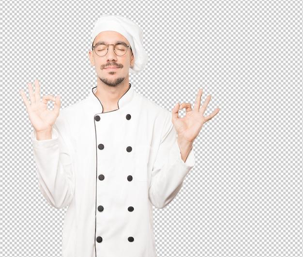 Szczęśliwy młody szef kuchni robi gestowi medytacja