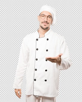 Szczęśliwy młody szef kuchni robi gestowi powitania z jego ręką
