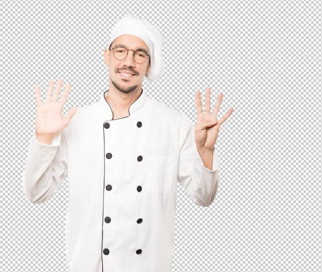 Szczęśliwy młody szef kuchni robi numerowi dziewięć gestowi z jego rękami