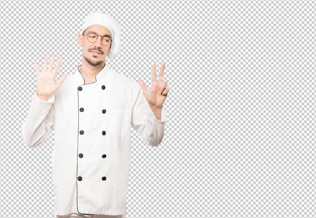 Szczęśliwy młody szef kuchni robi numerowi osiem gestowi z jego rękami
