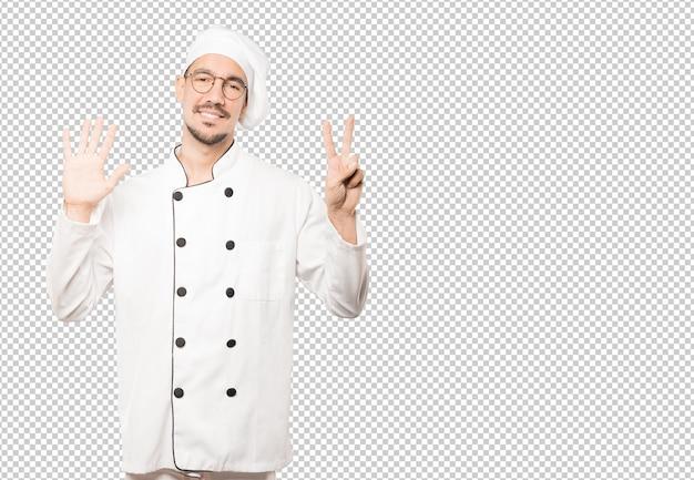 Szczęśliwy młody szef kuchni robi numerowi siedem gestowi z jego rękami