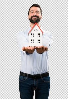 Szczęśliwy przystojny mężczyzna trzyma troszkę dom z brodą