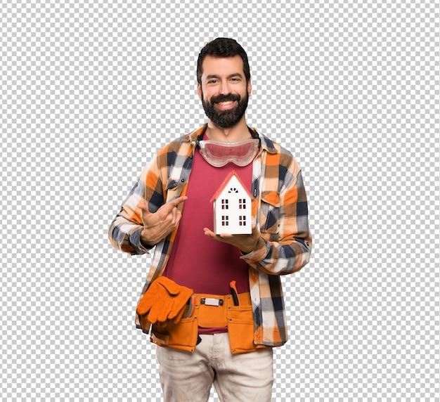 Szczęśliwy rzemieślnik mężczyzna trzyma małego dom