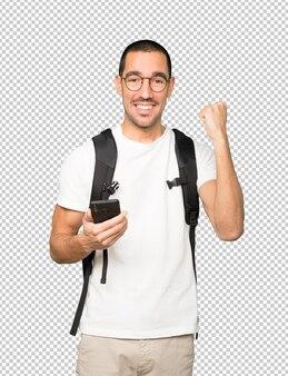 Szczęśliwy student korzystający z telefonu komórkowego i świętujący