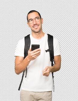 Szczęśliwy student patrząc w górę i za pomocą telefonu komórkowego