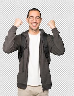 Szczęśliwy student robi konkurencyjny gest