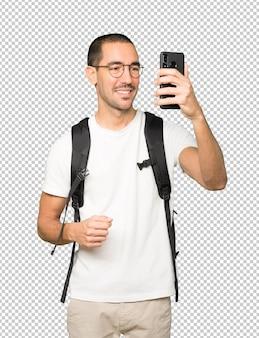 Szczęśliwy student robienia selfie z jego telefonu komórkowego