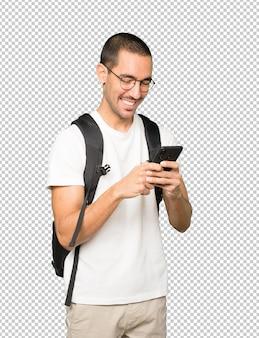Szczęśliwy student za pomocą swojego telefonu komórkowego