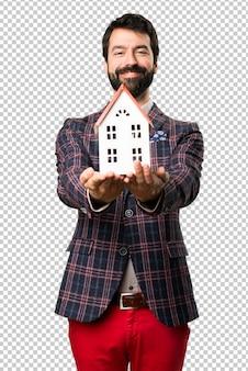 Szczęśliwy well ubierający mężczyzna trzyma troszkę dom