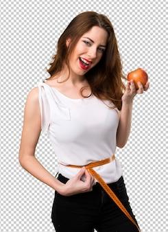 Szczupła kobieta z taśmy miarą i mieniem jabłko
