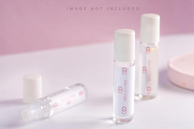 Szklane próbki perfum na opakowaniu produktu na różowym tle